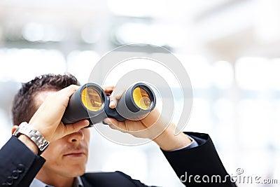 Uomo di affari con il binocolo che osserva al futuro