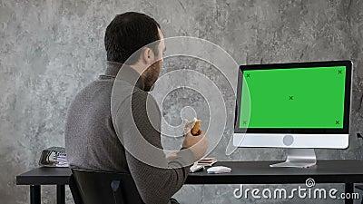 Uomo di affari nell'ufficio che mangia prima colazione, pranzo e guardante qualcosa sul mackintosh, computer Modello verde dello  video d archivio