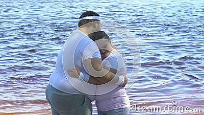 Uomo di peso eccessivo che abbraccia la sua amica grassottella sveglia vicino al fiume, alla tenerezza ed all'amore video d archivio