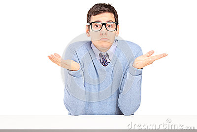 Uomo dubbioso che si siede e che gesturing con le mani