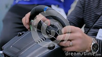 Uomo facendo uso della leva di comando del volante di gioco alla mostra di tecnologia archivi video