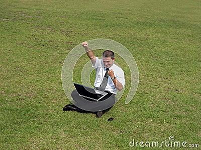 Uomo felice con il calcolatore nel campo
