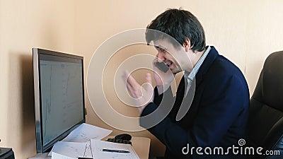 Uomo frustrato che lavora al computer e che chiama telefono cellulare Confronta i grafici sullo schermo e su carta archivi video