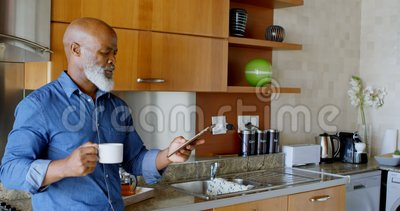 Uomo senior che per mezzo della compressa digitale mentre mangiando caffè nero in cucina 4k video d archivio