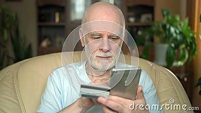 Uomo senior sorridente bello che si siede sulla sedia a casa Acquisto online con la carta di credito sullo smartphone archivi video