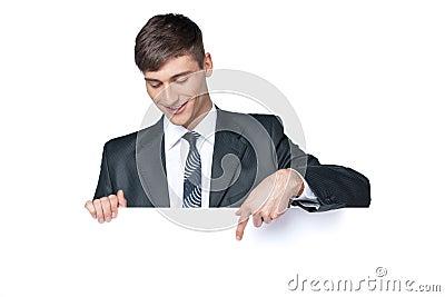 Uomo sorridente di affari che mostra qualcosa sul manifesto in bianco.