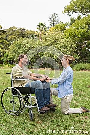 Uomo sorridente in sedia a rotelle con il partner che si inginocchia accanto lui