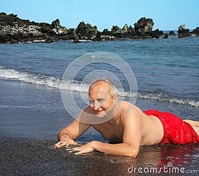 Uomo sulla spiaggia nera della sabbia