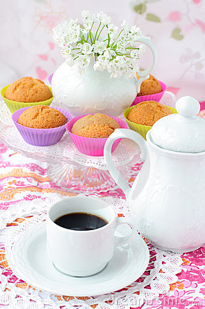 Сup of coffee with cupcakes at a background