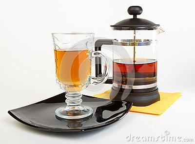 Сup of tea on black plate with teapot