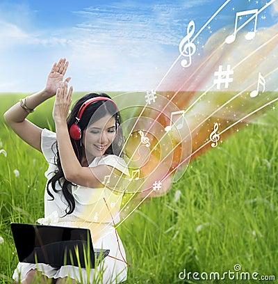 Upphetsad kvinnlig nedladdningmusik från den utomhus- bärbara datorn -