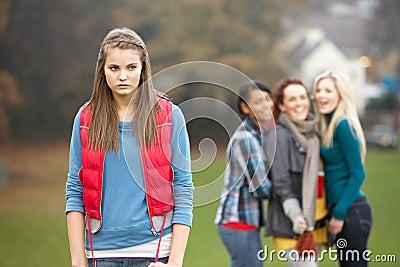 Upset Teenage Girl With Friends Gossiping