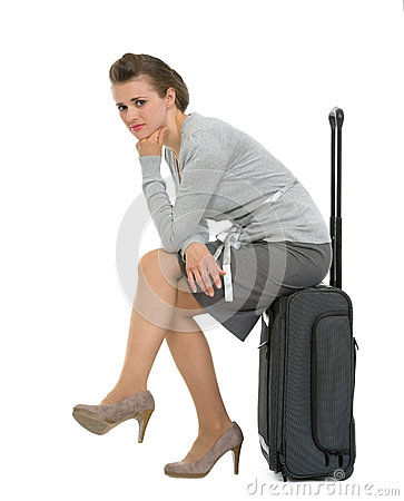 Upset traveling woman sitting on suitcase