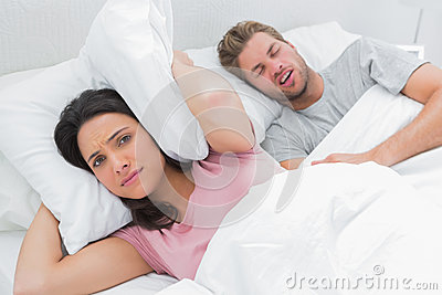 Upset woman covering ears with pillow next to husband snoring
