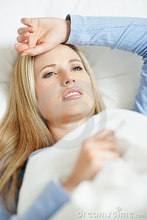 Upset woman having a migraine lying on bed at home