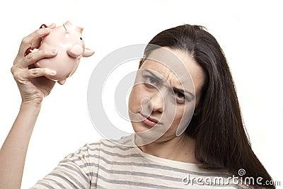 Upset woman with a piggy bank