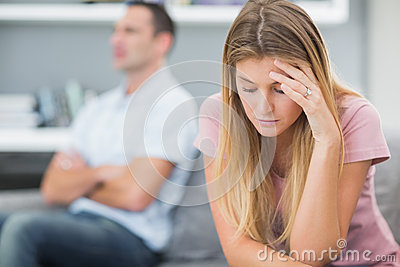 Upset woman thinking on couch after fight with husband
