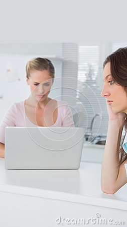 Upset woman thinking while her friend is typing