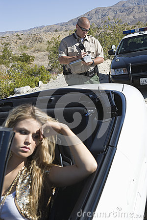 Upset Woman With Traffic Cop Writing Ticket