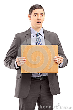 Upset young businessman in suit holding a piece of cardboard