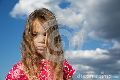 Upset Young Girl against Cloudy Sky