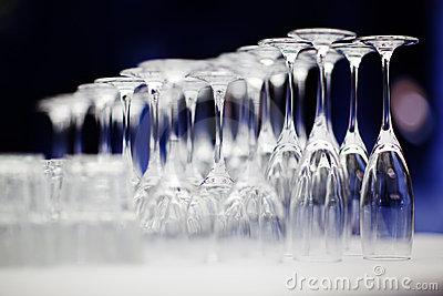 Upturned set of wine glasses on blurred blue