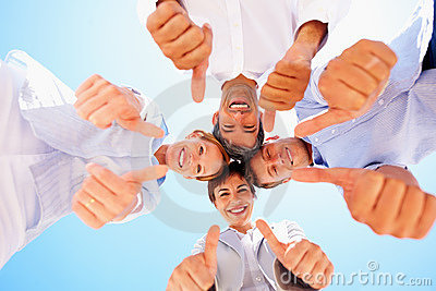 Upward view of business people with thumbs raised