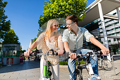 Urban couple riding bike in free time in city
