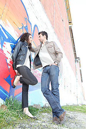 Urban couple standing by wall