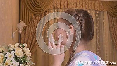 Urocza mała dziewczynka, przyklejająca błyszczące gwiazdy na twarzy w domu zbiory wideo