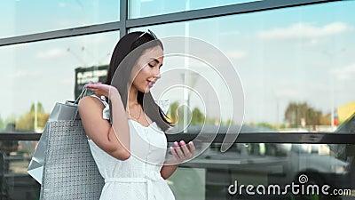 Urocza moda trzymająca torbę na zakupy za pomocą smartfona na szybie zdjęcie wideo