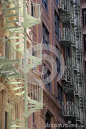 Ursnygg sikt av spiraltrappuppgångar på stadsbyggnader