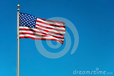 US American flag waving in wind with blue sky