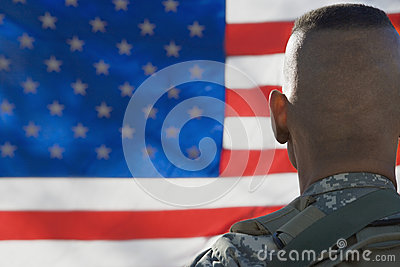 US Army Soldier Looking At Flag