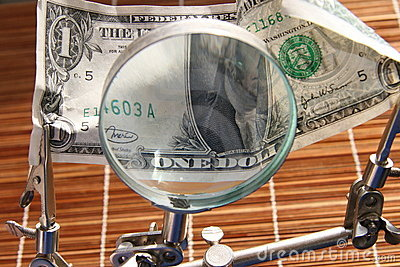 US dollar and magnifying glass