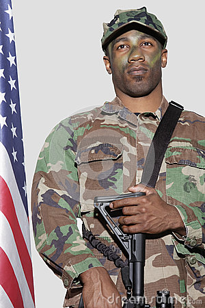 US Marine Corps soldier with M4 assault rifle standing by American flag over gray background