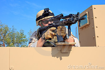 US Navy EOD aims rifle from a military humvee Editorial Image