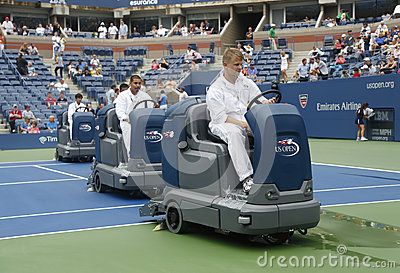 US Open cleaning crew drying tennis court after rain delay at Arthur Ashe Stadium Editorial Photo