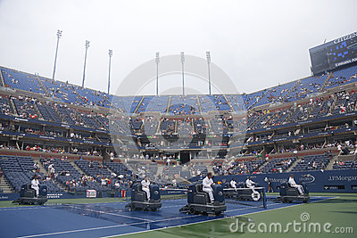US Open cleaning crew drying tennis court after rain delay at Arthur Ashe Stadium Editorial Photography