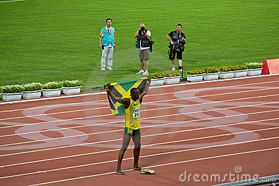 Usain Bolt celebrates with Jamaican flag Editorial Photography