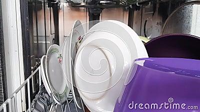 Usando una lavastoviglie moderna in casa, le mani della casalinga prendono i piatti puliti dalla lavastoviglie, da vicino Casa mo stock footage