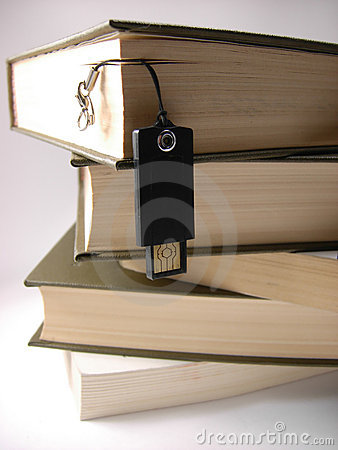 USB flash drive hanging in front of books.