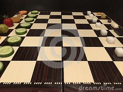 Useful and harmful foods play chess. Junk foods vs Vegetables Stock Photo