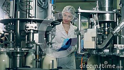 Usine laitière au travail avec une employée qui l'observe clips vidéos