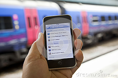 Using a UK Train Timetable App Editorial Stock Image