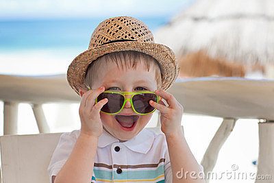 Сute toddler boy playing with sunglasses
