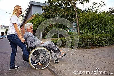 Utente di sedia a rotelle d aiuto della donna