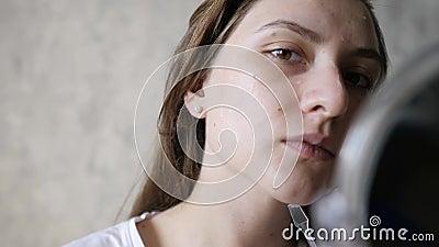 Utilisation de la crème faciale La belle femme applique du gel hydratant, sourit et regarde l'appareil photo Gros plan, tir stati banque de vidéos
