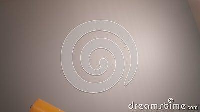 Utilizar un rodillo de pintura amarillo transparente en la pared blanca almacen de video