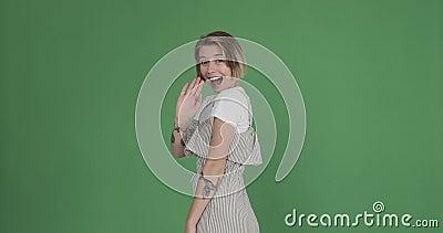 Utmärkt kvinna som viftar hand och som hälsar på grön skärm